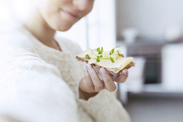 Dame som spiser knekkebrød med ost og urter.
