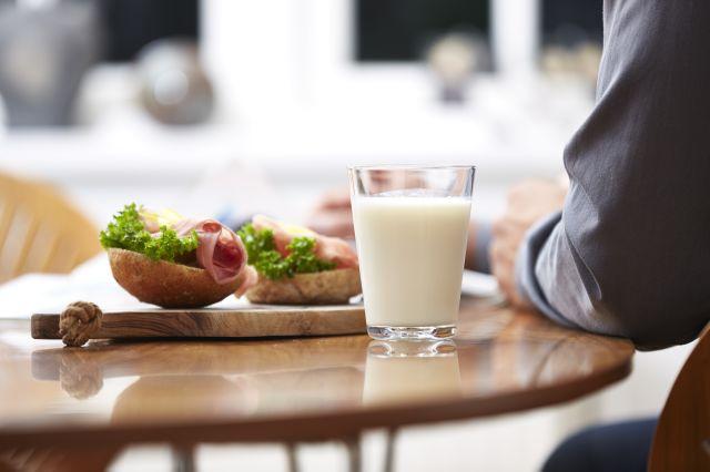 Ser armen til en mann som sitter ved et bord med en fjøl med to halverundstykker med skinke og salat og et glass melk.