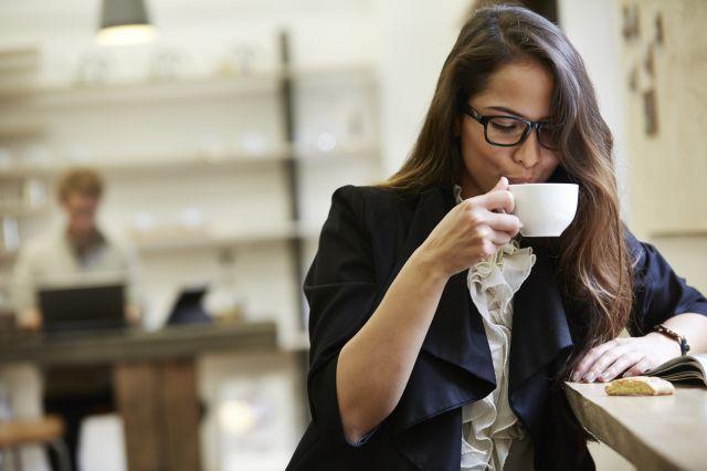 Dame med mørkt hår og briller som sitter på kafe og leser og drikker kaffe fra en hvit kopp.