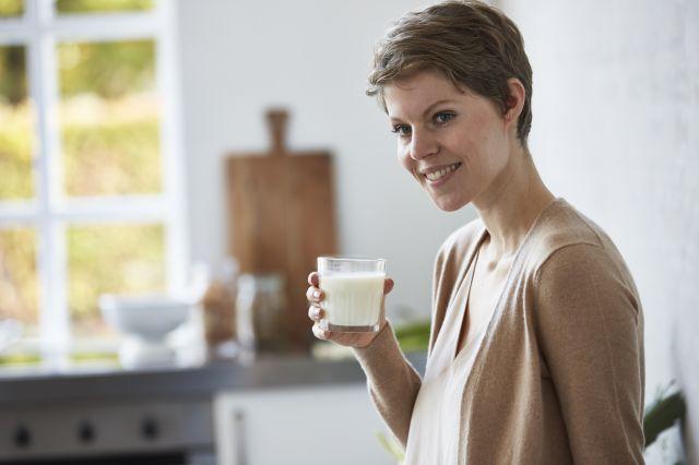 En dame som står på et kjøkken og smiler med et glass melk i hånden.