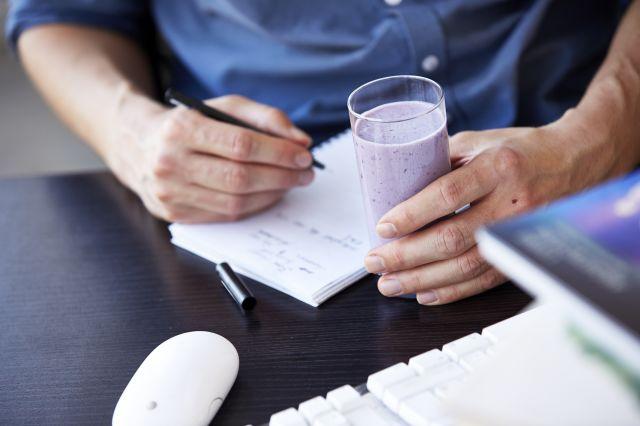Mann som sitter og skriver med et melkeglass i hånden.