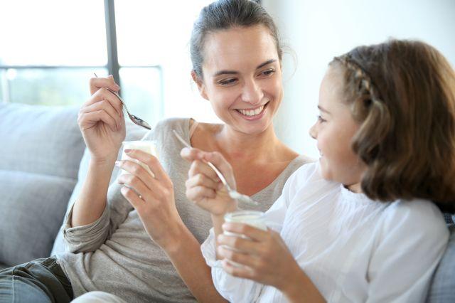 Dame og jente som sitter ved siden av hverandre i en sofa og smiler og spiser yoghurt.