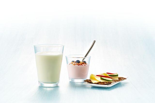 Ett glass melk, et glass med yoghurt, müsli og bær og et knekkebrød med gulost, agurk og paprika.