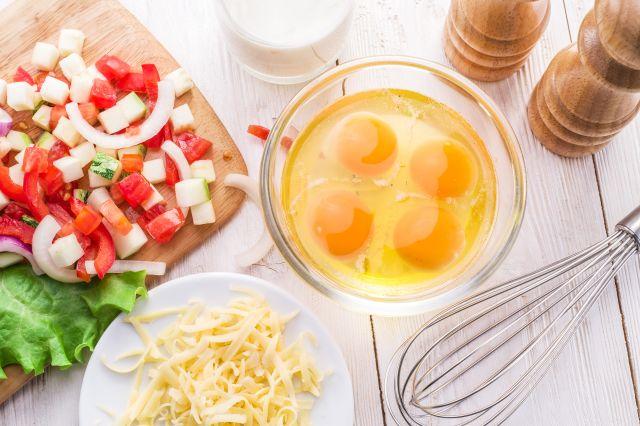 Grønnsaker på en fjøl, egg som er knust i en bolle, revet ost og et glass melk på en kjøkkenbenk.