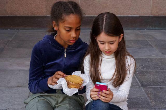 To jenter ser på mobil og spiser matpakke