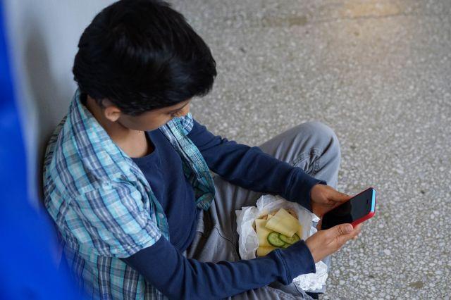 Gutt med matpakke og mobil