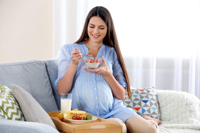 Gravid dame som sitter i sofaen og spiser musli med melk og bær.
