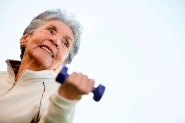 Eldre dame som smiler og løfter en håndmanual med den ene hånden.