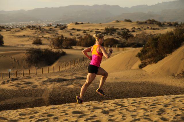 Dame løper på sand
