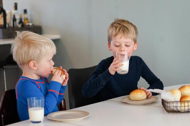 Gutter som spiser boller og drikker melk