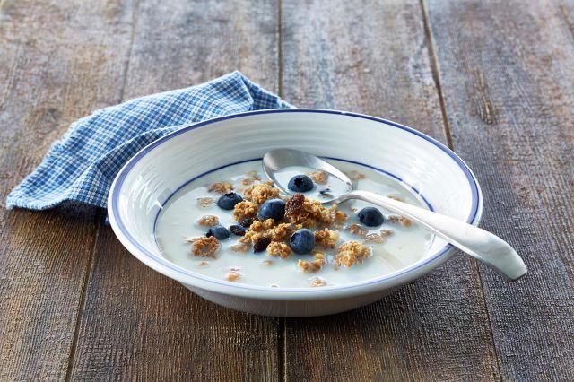En skål med melk og kornblanding med blåbær.