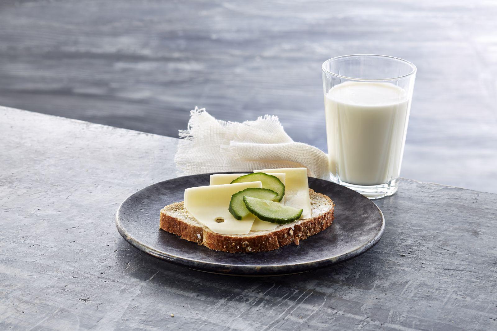 Brødskive med gulost og agurk og et glass melk.