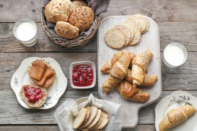bord med scones, fylte horn, havrekjeks, syltetøy og melk