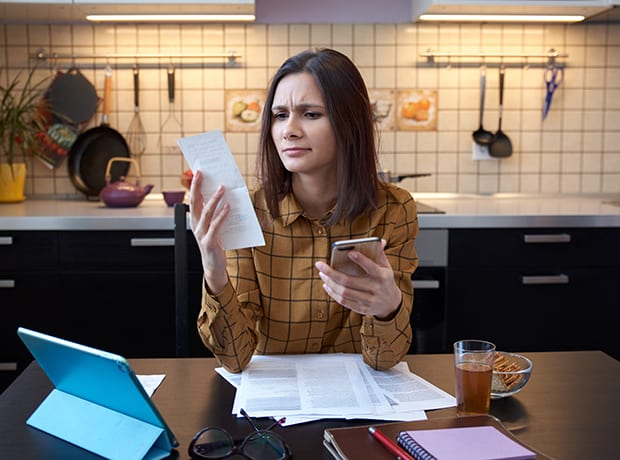 Woman looking at receipts with computer and smartphone