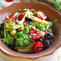 Ensalada de pasta con verduras, queso y aceitunas negras robiola