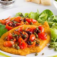 Chuleta con las aceitunas, las alcaparras y tomates cherry