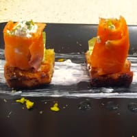 Crostini with smoked salmon rolls, philadelphia and pistachios