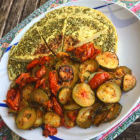 savory pancakes with semolina served with zucchini and cherry tomatoes