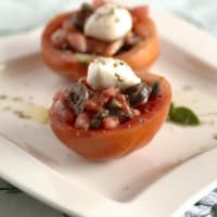 Los tomates crudos rellenos de ovoline búfalo, las aceitunas griegas y orégano