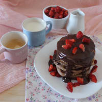 Pancakes with chocolate sauce and strawberries