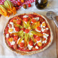 Full-length pizza with cottage cheese, cherry tomatoes and pumpkin flowers