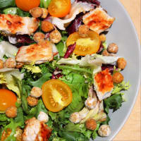 Salad with turkey on plate, cherry tomatoes and crispy chickpeas