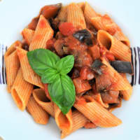 Pasta corta con sugo di pomodoro, melanzane, olive e basilico fresco