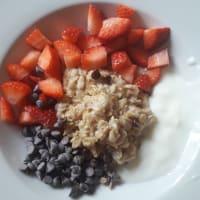 Porridge con fragole, gocce di cioccolato e yogurt