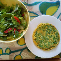 Omelette with rocket accompanied by salad with rocket and date tomatoes