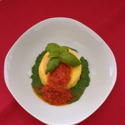 Polenta pie with vegetarian sauce on spinach cream