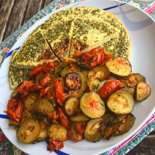 Pancake salato con semola rimacinata servito con zucchine e pomodorini