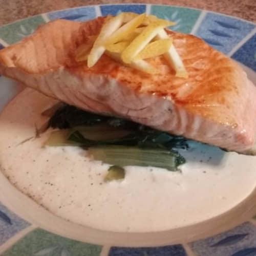 Chamuscado salmón sobre una cama de espinacas y salsa de ajo