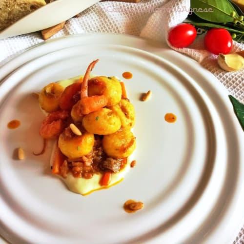 Gnocchi Misto Mare con piñones tostados sobre un lecho de patatas all'asiago