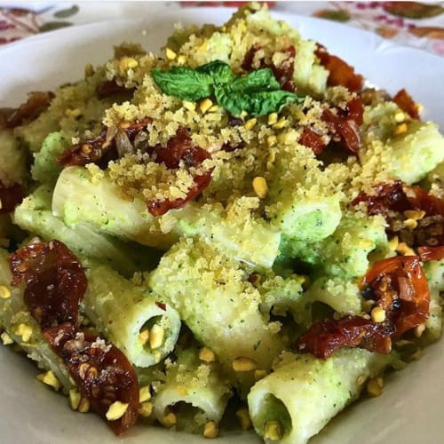 Sprinkle with zucchini pesto, dried tomatoes, crumbs and pistachios