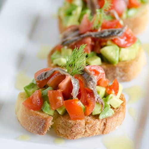 Crostini with avocado, cherry tomatoes and anchovies