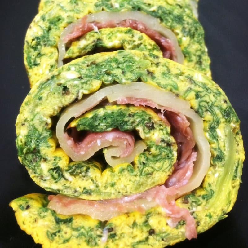Rollo de tortilla rellena de queso de espinacas y salami