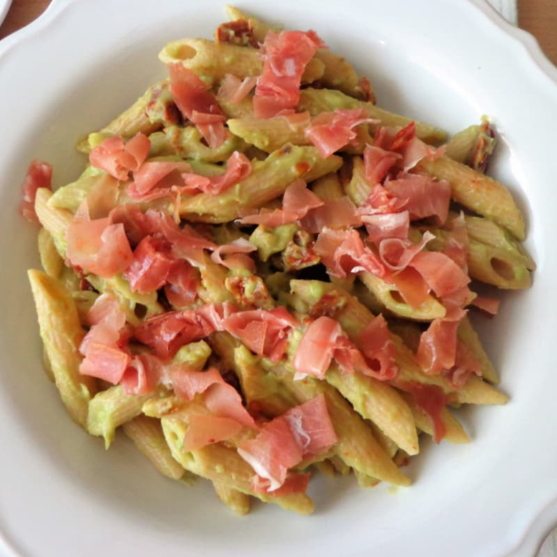 Penne with avocado sauce, dried tomatoes and raw ham