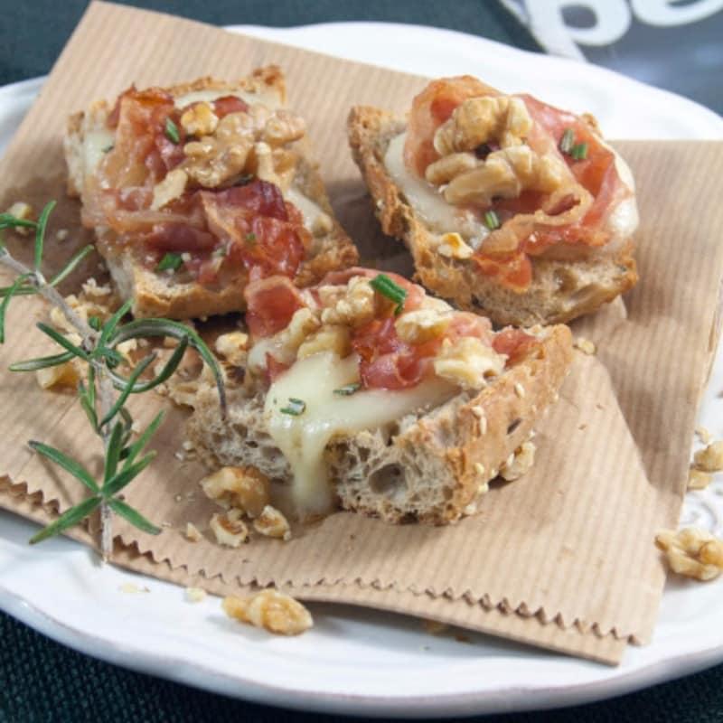 Crostini con Taleggio queso, tocino, miel y frutos secos