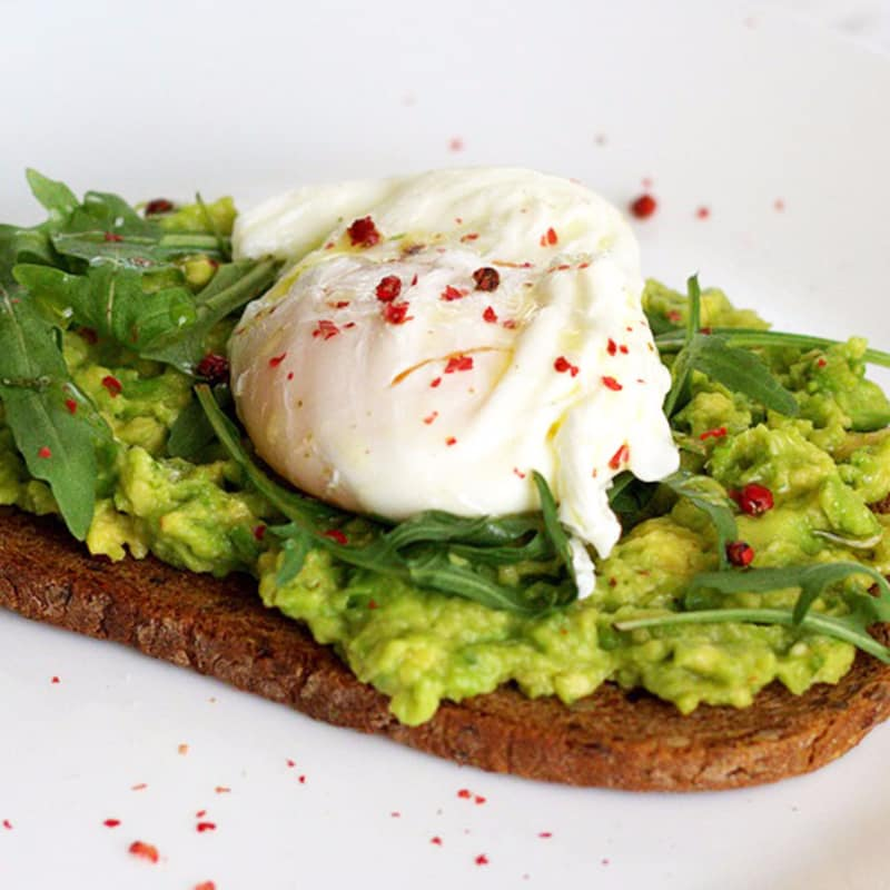 Avocado toast with poached egg, oil, lemon and pink pepper