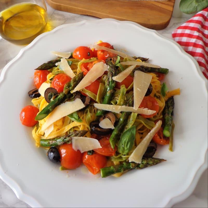 Tallarines verdes y amarillas con espárragos, tomates cherry y aceitunas negras