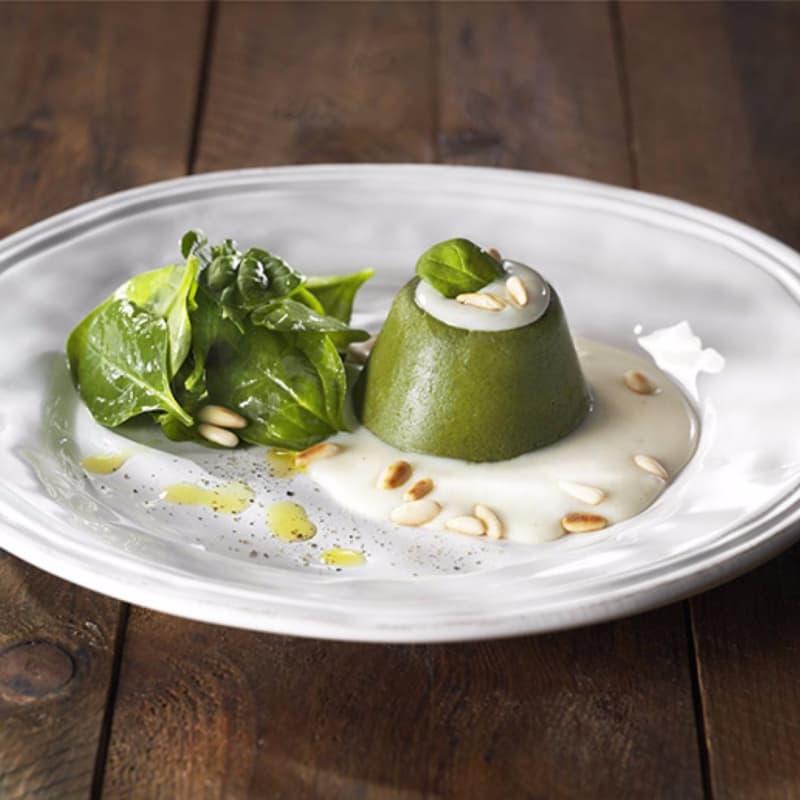 Flan di spinaci su fonduta di parmigiano, insalatina e pinoli