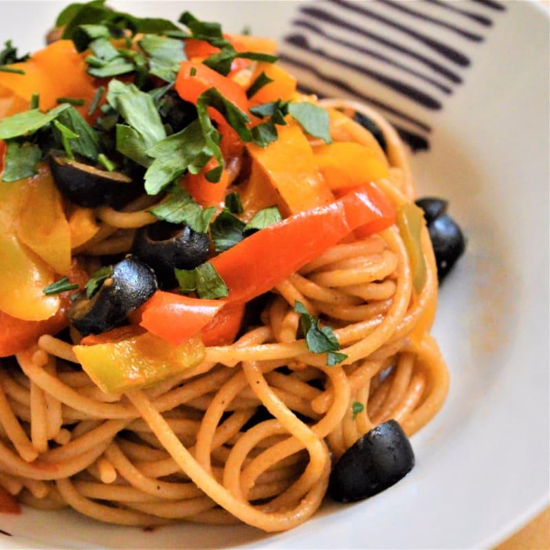 espaguetis integrales con una salsa de pimientos y aceitunas negras