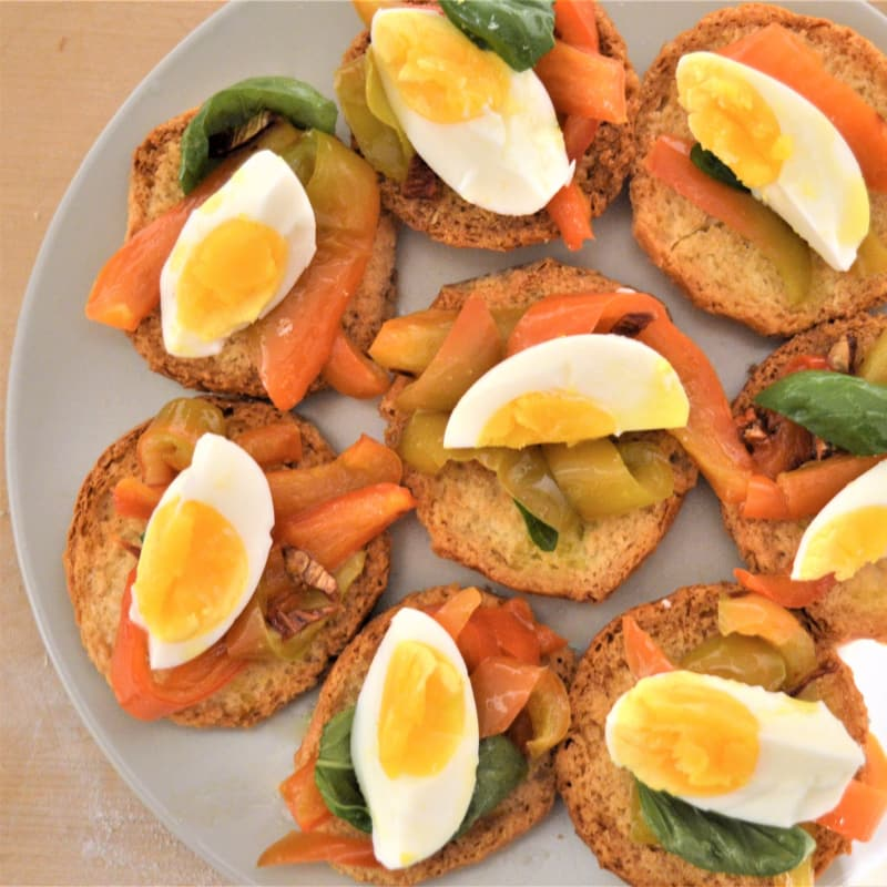 Frise con peperoni saltati, pomodori secchi, uova sode e basilico