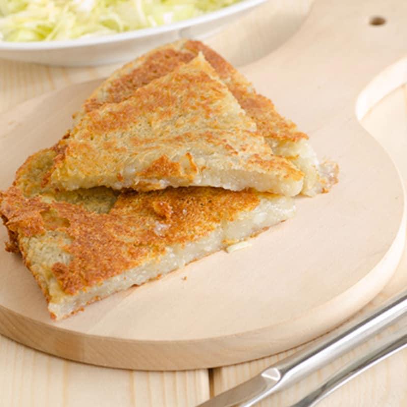 Pastel o crepe de patata de finales de los años veinte con queso Asiago y el tocino
