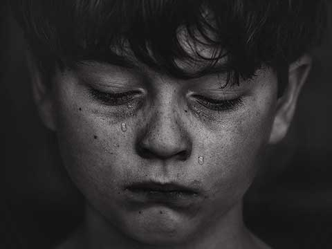 Crying child looking down