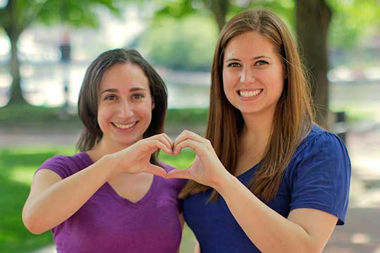 Two Smiling Women forming heart with their hands