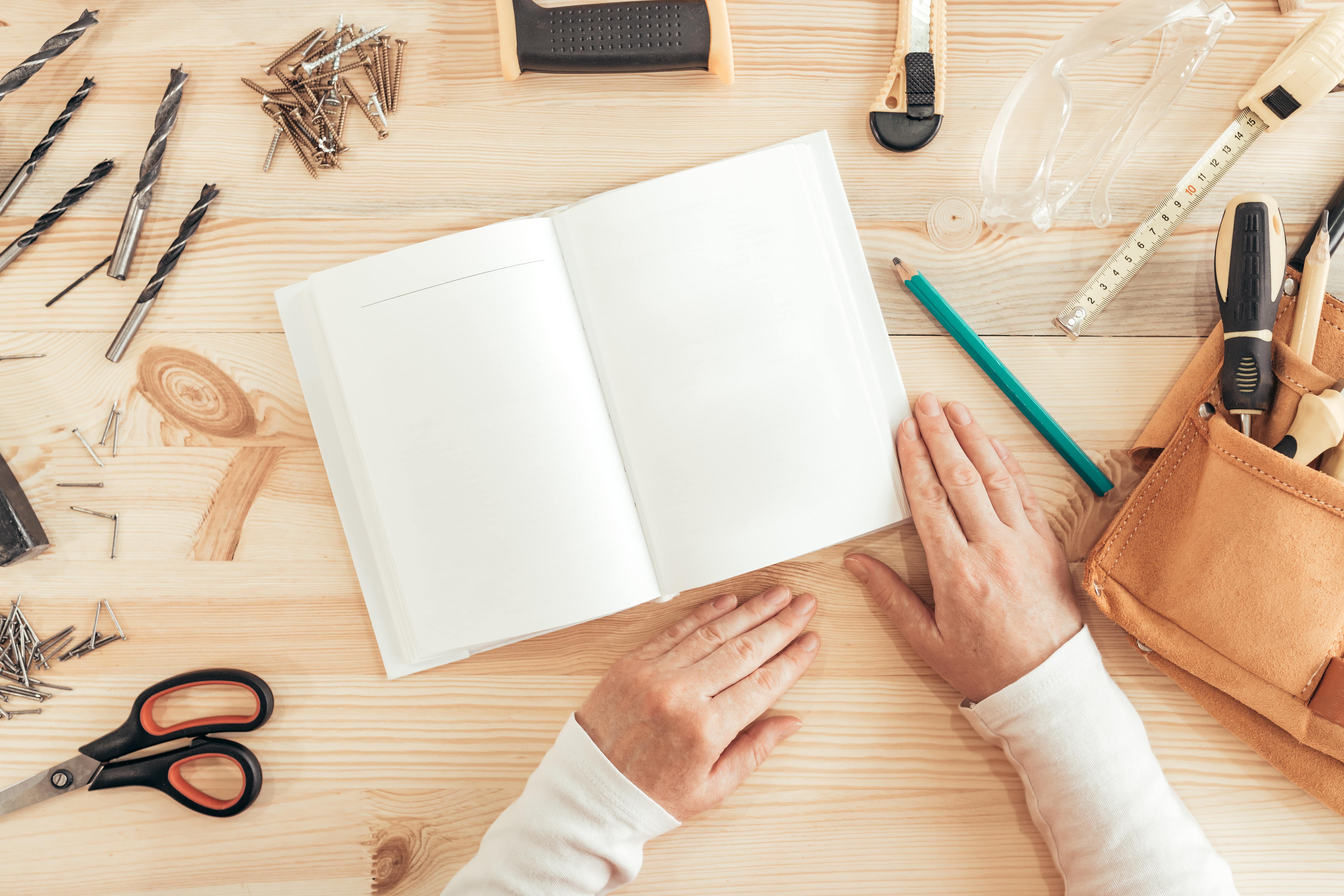 Personne devant une page blanche de cahier sur un plan de travail