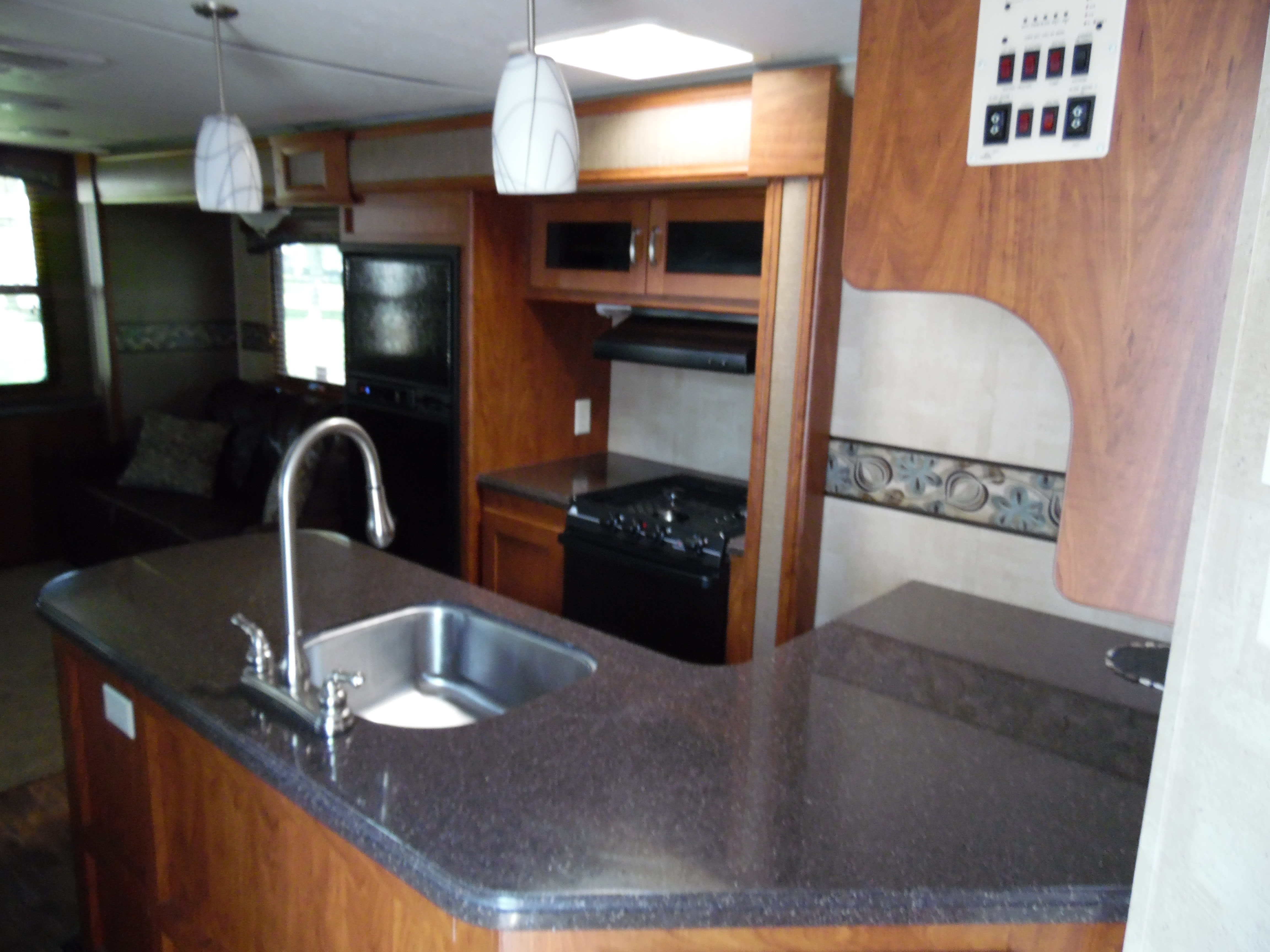 Corian countertop large basin sink pull out faucet with overhead bar lights. Keystone Passport Ultra Lite Elite 2014