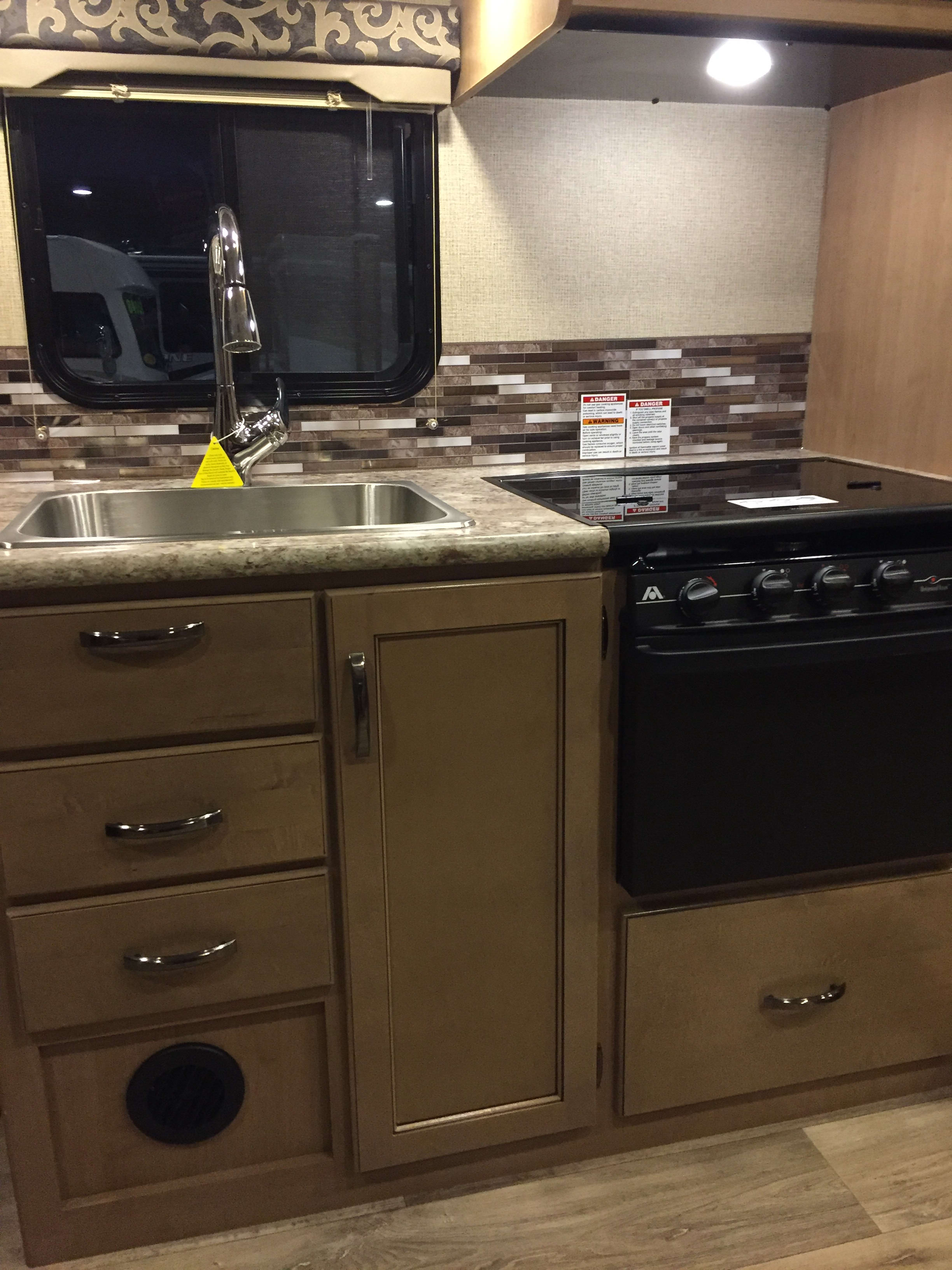 Kitchen with full size sink and 3 burner stove, oven and microwave. Thor Motor Coach 24F 2018