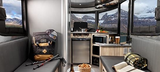 The inside features a bath/shower, sink, propane stove, microwave, plenty of storage and a versatile floor plan. The benches and dining area convert into a large sleeping area. . Airstream Base Camp 2017